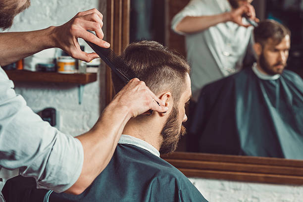die hände der jungen friseur macht frisur, attraktive mann - männerfrisuren stock-fotos und bilder