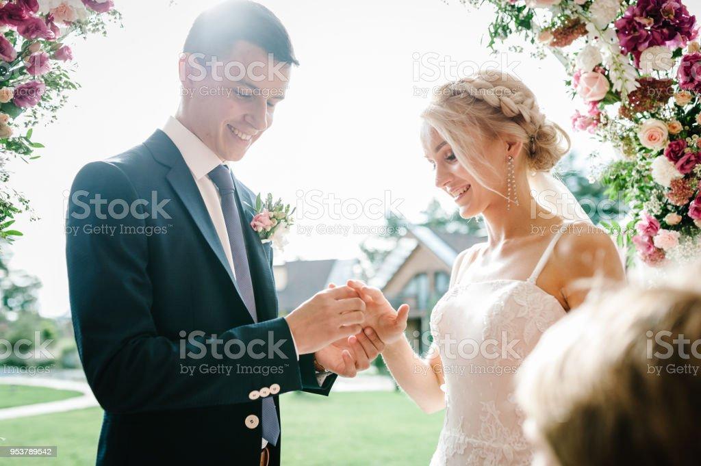 Der schöne Bräutigam trägt einen Hochzeit goldene Verlobungsring am Finger der attraktiven Braut im Freien. Brautpaar. Hochzeit Zeremonie unter dem Bogen dekoriert mit Blumen und grün. – Foto