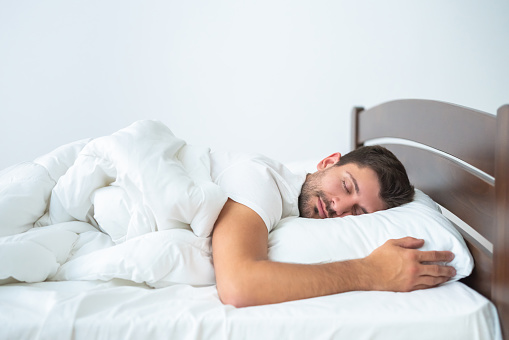 istock The handsome man sleeping on the bed on the white background 1077191096