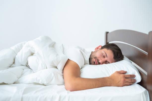 el hombre guapo durmiendo en la cama sobre el fondo blanco - man sleeping fotografías e imágenes de stock