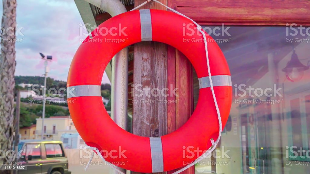 The hanging orange silver bouy on the window in Italy stock photo