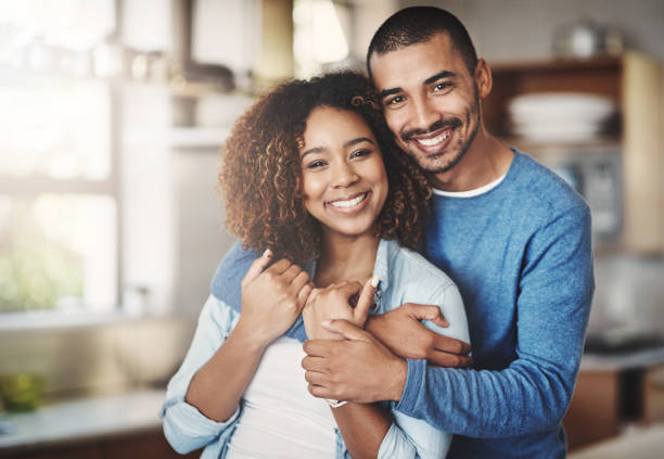 The happiest hearts make the happiest homes Portrait of a happy young couple in their kitchen at home husband stock pictures, royalty-free photos & images