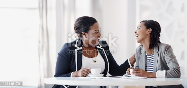 Cropped shot of two attractive young businesswomen having a laugh while working together in their office