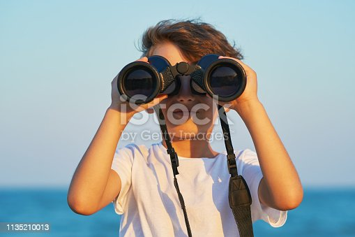 istock The happy boy holds a big binoculars and looks into the distance and something joyfully screams in the blue sky against the blue sea and the blue sunset of a sunny day 1135210013