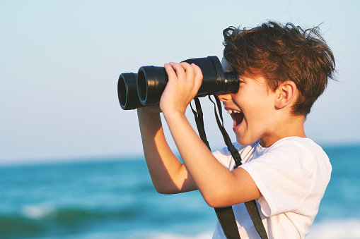 The happy boy holds a big binoculars and looks into the distance and something joyfully screams in the blue sky against the blue sea and the blue sunset of a sunny day