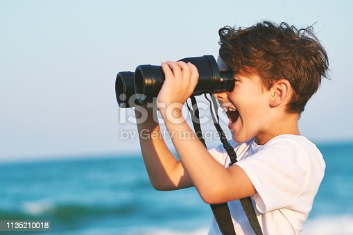 istock The happy boy holds a big binoculars and looks into the distance and something joyfully screams in the blue sky against the blue sea and the blue sunset of a sunny day 1135210018