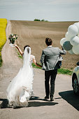 The happy bride and groom hold the balloons and walk back after the wedding ceremony. The best marriage day. A newlywed wedding couple running on a country straight road for their honeymoon.