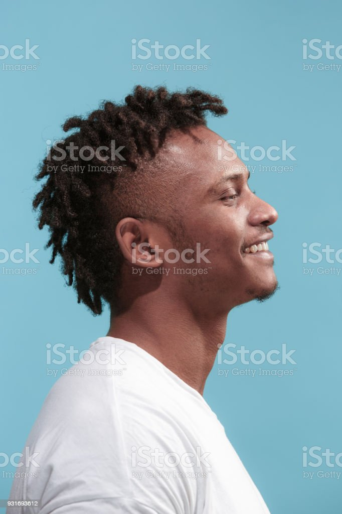 The happy business Afro-American man standing and smiling against blue background. Profile view - fotografia de stock