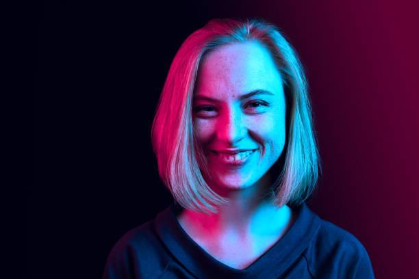 행복 한 비즈니스 여자 서 있고 네온 배경에 대 한 미소. - 형광색의 뉴스 사진 이미지