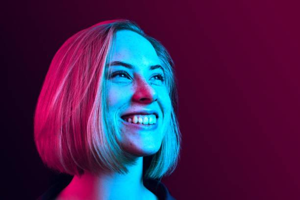 快樂的女商人站在霓虹燈的背景下微笑著。 - 霓虹色 個照片及圖片檔