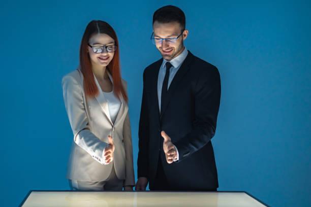 the happy businessman and a businesswoman working with a screen - business woman hologram imagens e fotografias de stock