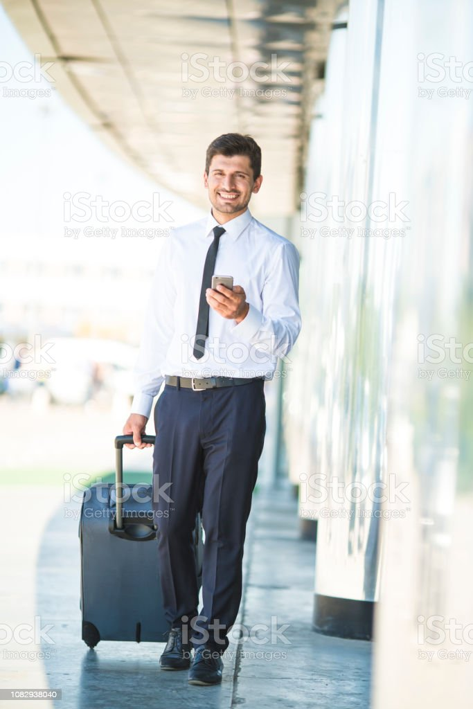 The happy businessman phone and walk with a suitcase near building