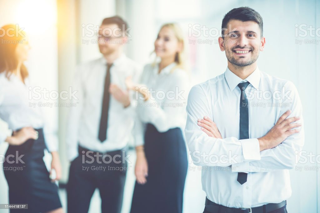 The happy businessman stand near partners on the sunny background