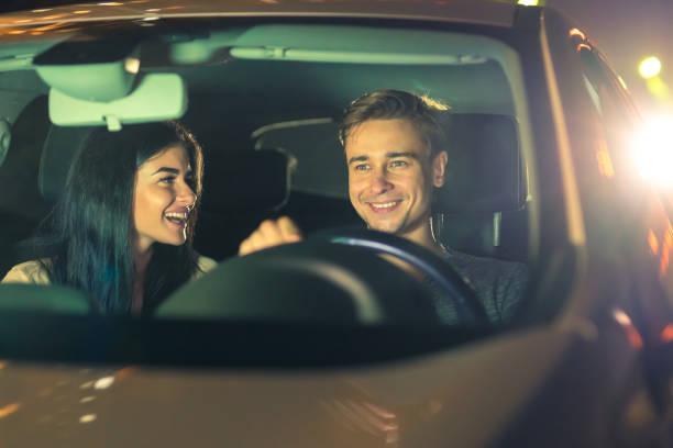 les couples heureux conduisent une voiture. soirée soir - voiture nuit photos et images de collection
