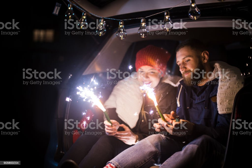 The happy couple hold a firework sticks. evening night time stock photo