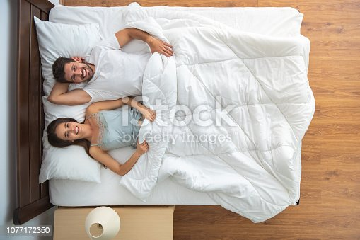 504371332 istock photo The happy couple laying on the bed. view from above 1077172350
