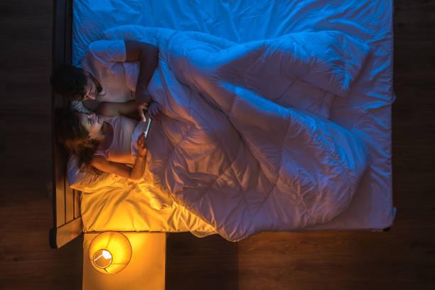 das glückliche paar mit einem telefon lag auf einem bett. abendliche nachtzeit. blick von oben - nachttischleuchte touch stock-fotos und bilder