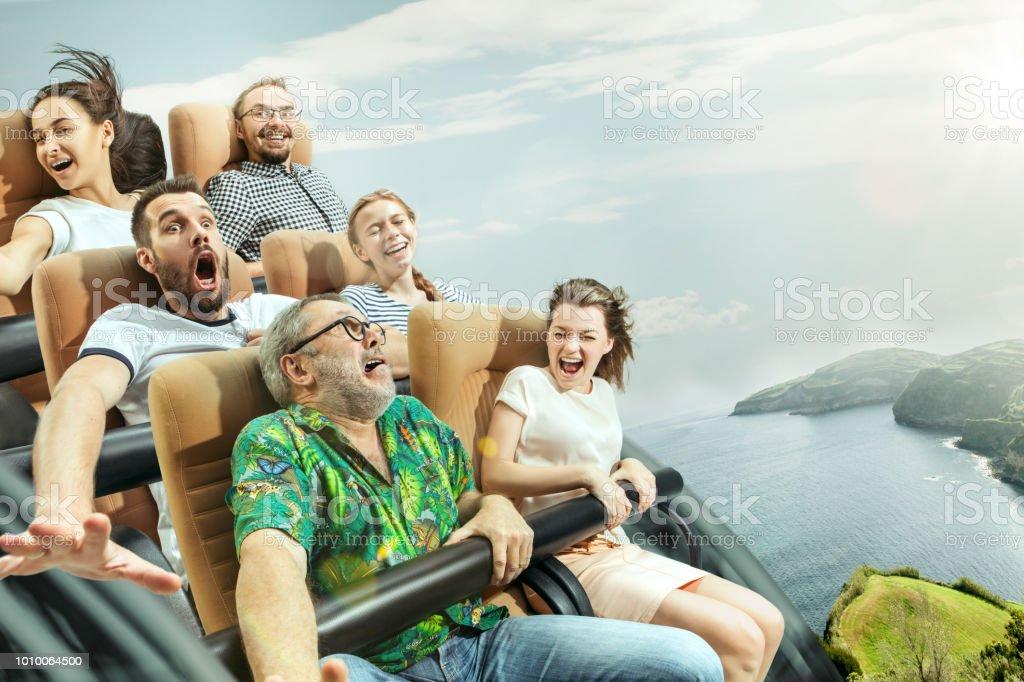 Die glücklichen Gefühle von Männern und Frauen, die gute Zeit auf einer Achterbahn im park – Foto