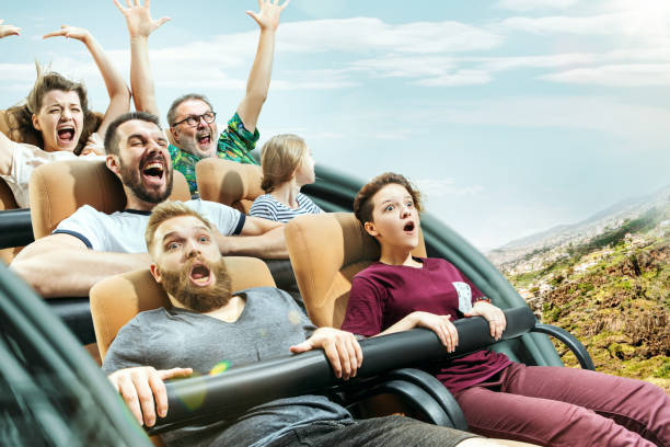 the happy emotions of men and women having good time on a roller coaster in the park - roller coaster stock pictures, royalty-free photos & images
