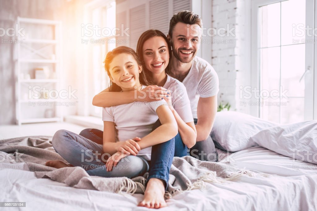 The happy family sitting on the bed stock photo