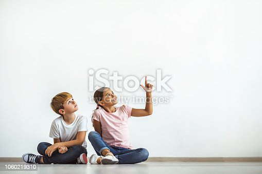 The happy girl and a boy sitting on the floor and gesturing