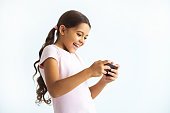The happy girl holding a phone on the white wall background