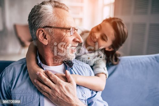 istock The happy girl hugs a grandfather on the sofa 986705988