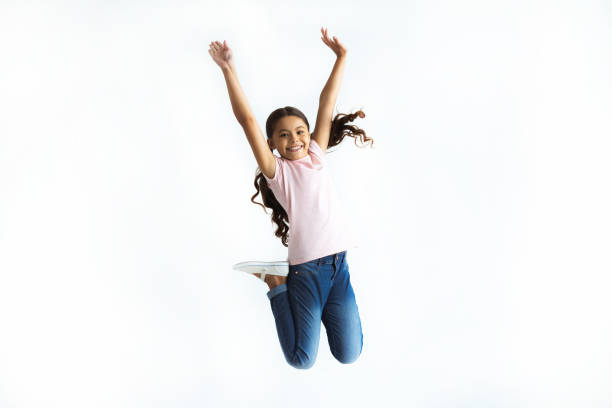 The happy girl jumping on the white wall background The happy girl jumping on the white wall background mid air stock pictures, royalty-free photos & images