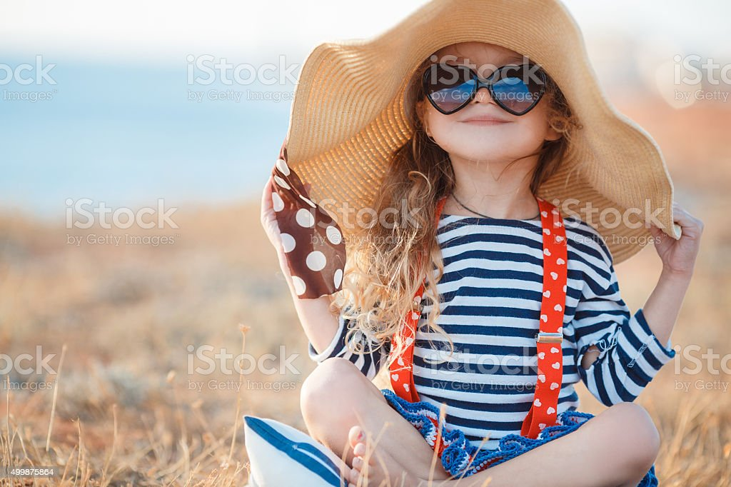 The happy little girl in a big hat stock photo