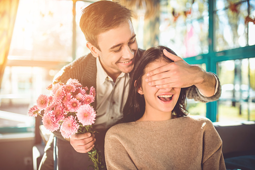 The happy man make a surprise with flowers for a girlfriend in the restaurant