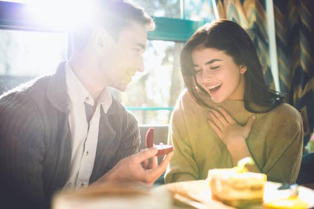 den lyckliga mannen gör ett förslag till sin flickvän i restaurangen - förlovningsring bildbanksfoton och bilder
