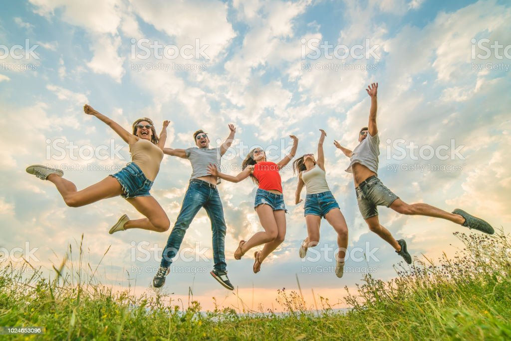 The happy people jumping on the background of the clouds