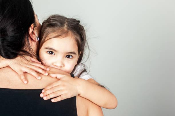 The Happy Small Girl Hugs Mom stock photo