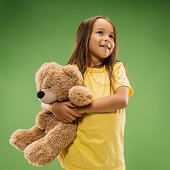 Happy teen girl standing, smiling with toy bear isolated on trendy studio background. Beautiful female portrait. Young satisfy girl. Human emotions, facial expression concept. Front view.