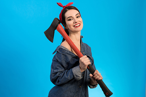 The happy woman holding the axe on the blue background