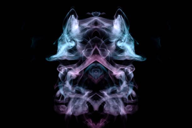 神秘動物或昆蟲的頭,以綠色和粉紅色捲曲的煙霧的形式,在黑色背景上大眼睛。列印衣服。圖像檔