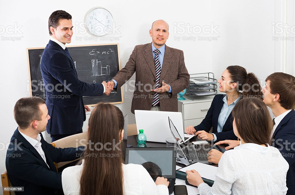 The head of office greeting new young partner stock photo