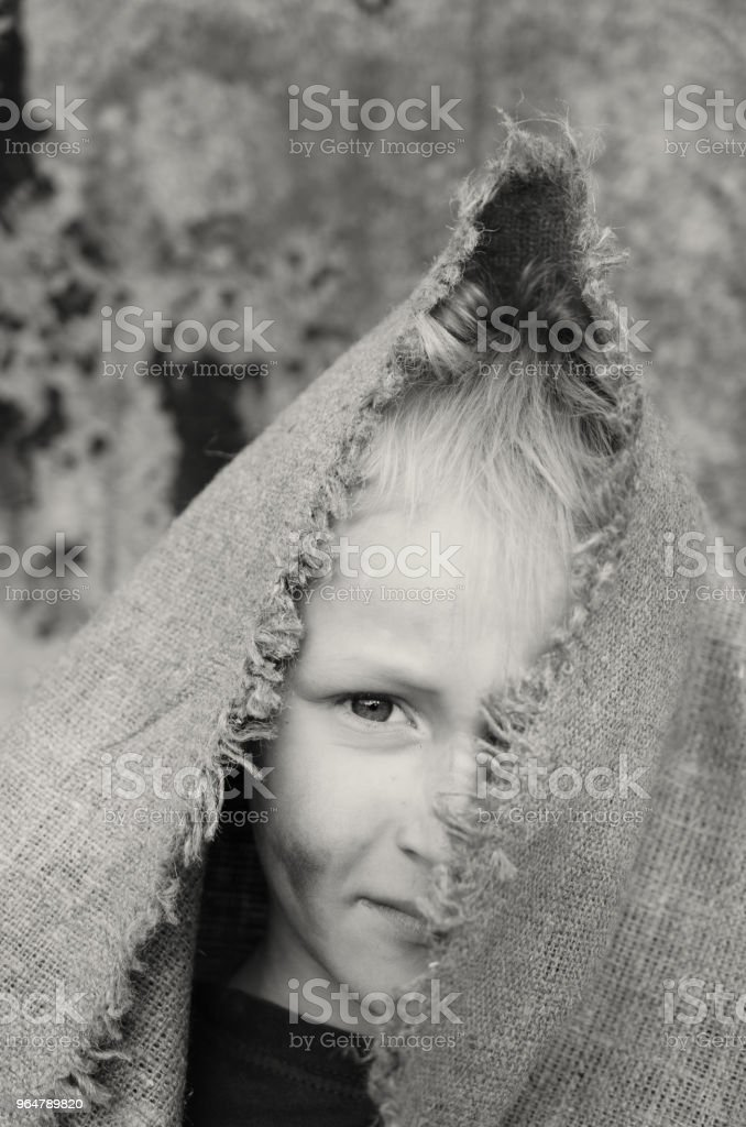The head portrait of a poor boy. Head in a sackcloth. Emotions. royalty-free stock photo