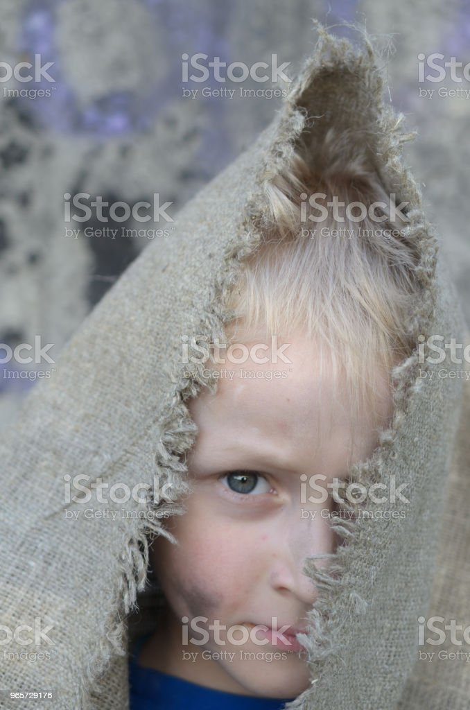 The head portrait of a poor boy. Head in a sackcloth. Emotions