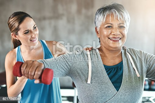 Shot of a senior woman using weights with the help of a physical therapist