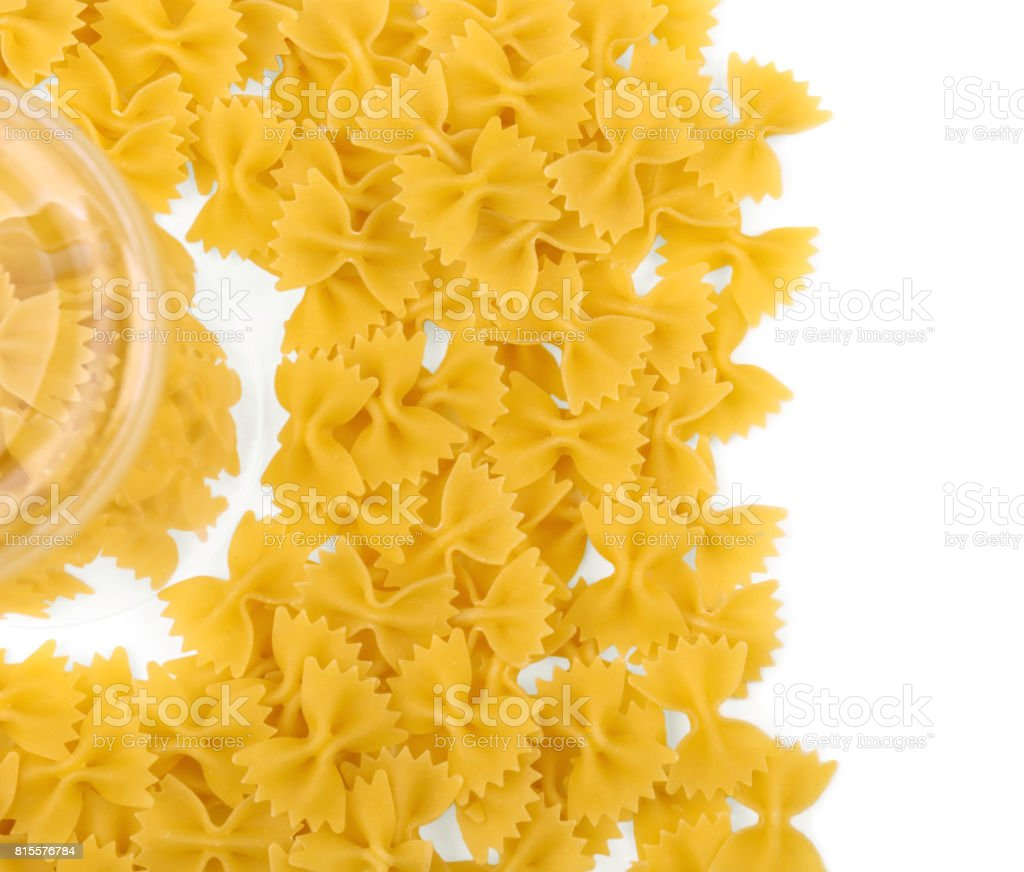 The heap of farfalle pasta a top view, isolated on a white background. Many farfalle pasta near a transparent glass. Delicious traditional farfalle Italian macaroni. stock photo