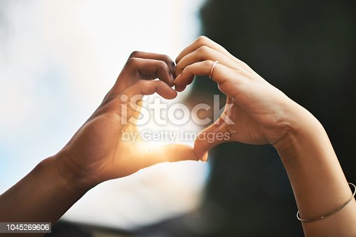 Cropped shot of a couple making a heart gesture with their hands outdoors