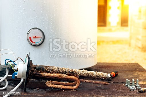 the heating element is covered with rust and scale, with screws on the background of the boiler, lying on a wooden table.