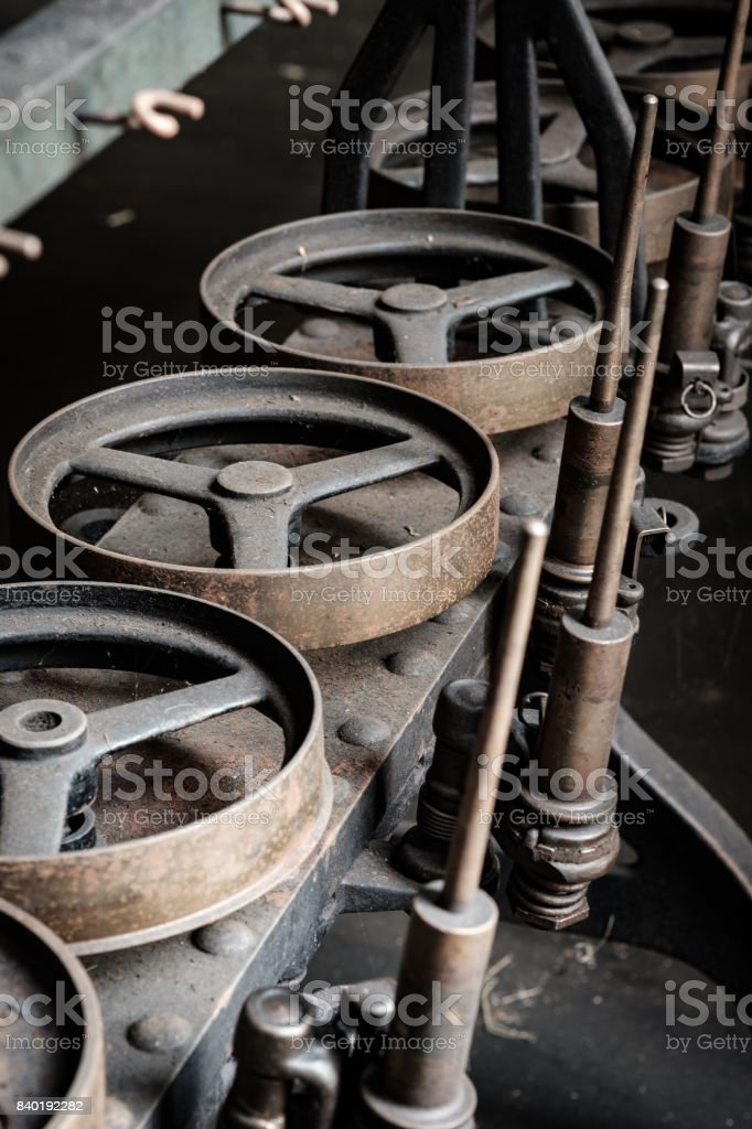 The heavy gears, spindles and wheels used on old silk mill and embroidery mill stock photo