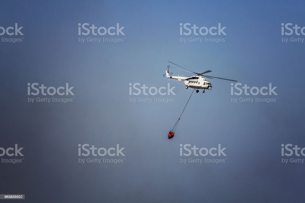 The helicopter extinguishes large forest fires. The fire helicopter delivers water to the fire. Multipurpose helicopter in flight with a hanging and drainage fire extinguishing device stock photo