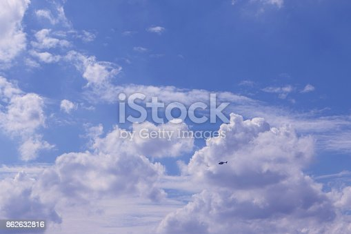 925925874 istock photo The helicopter Fly in bright blue sky with a big white clouds on a beautiful day 862632816