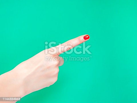 istock The Hey You Hand Sign Look At This Sign. Female hand finger pointing isolated on bright turquoise background. 1144334943