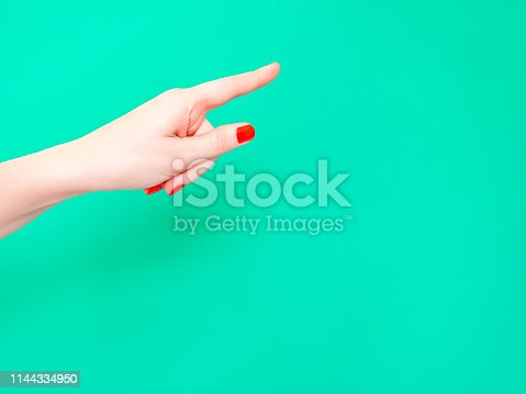 istock The Hey You Hand Sign Look At This Sign. Female hand finger pointing isolated on bright turquoise background. 1144334950