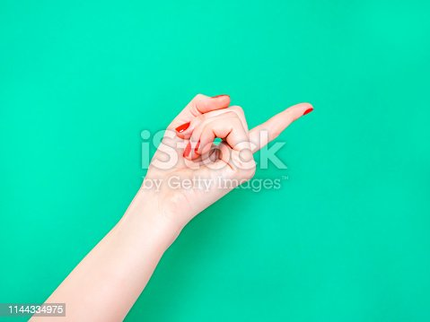istock The Hey You Hand Sign Look At This Sign. Female hand finger pointing isolated on bright turquoise background. 1144334975