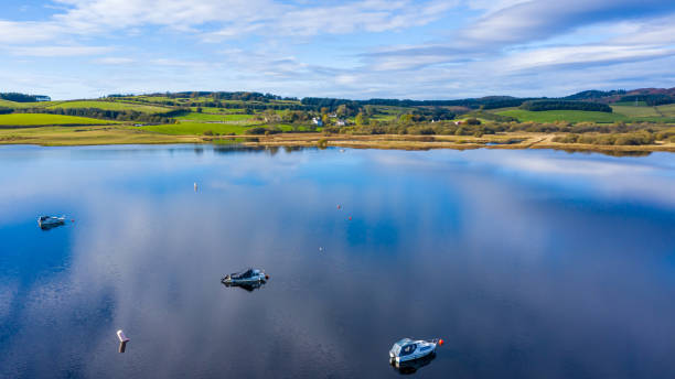 The high angle aerial view of a slow moving river in rural Dumfries and Galloway south west Scotland The view from a drone of a stretch of Scottish river that is flowing out out of a loch. It is early autumn and autumn colours are stating to show on the plants and trees. johnfscott stock pictures, royalty-free photos & images